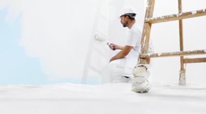 Maler streicht Wand weiß