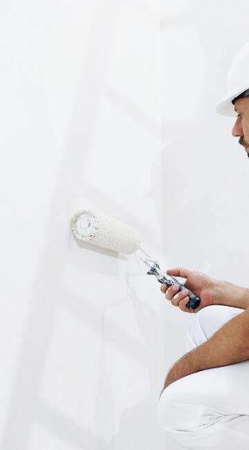 Maler streicht eine weiße Wand