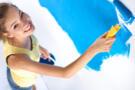 Frau streicht Wand blau