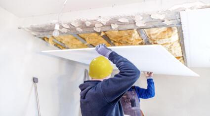 Zwei Bauarbeiter dämmen die Decke